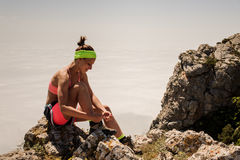 Young fitness woman trail runner tying shoelace at mountain top Royalty Free Stock Images