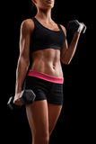 Young fitness woman in training pumping up muscles with dumbbell stock photo