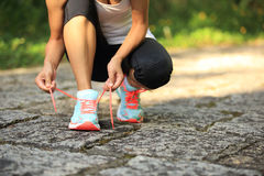 Young fitness woman tying shoelaces Stock Images