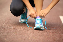 Young fitness woman tying shoelaces Royalty Free Stock Photos