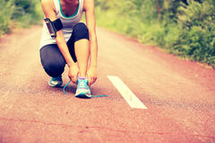 Young fitness woman tying shoelaces. On country road royalty free stock photography