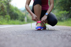 Young fitness woman tying shoelaces. On country road Stock Photo