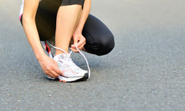 Young fitness woman tying shoelaces outdoor Royalty Free Stock Photos