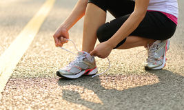 Young fitness woman tying shoelaces outdoor Royalty Free Stock Photo