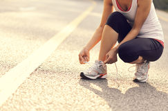 Young fitness woman tying shoelaces outdoor Royalty Free Stock Photography