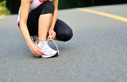 Young fitness woman tying shoelaces outdoor Royalty Free Stock Images