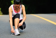Young fitness woman tying shoelaces Stock Photos