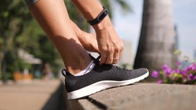 Young Fitness Woman Tying Sneakers Running Shoe Laces in Park. 4K, Close Up. Bangkok, Thailand. Young Fitness Woman Tying Sneakers Running Shoe Laces in Park stock footage