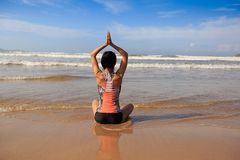 Fitness woman wear swimsuit practice yoga on the beach Stock Photography