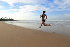 Fitness woman wear swimsuit running on beach. Young fitness woman wear swimsuit running on beach Stock Image