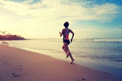 Fitness woman wear swimsuit running on beach. Young fitness woman wear swimsuit running on beach Stock Images