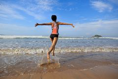 Fitness woman wear swimsuit running on beach. Young fitness woman wear swimsuit running on beach Stock Photography