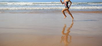 Fitness woman wear swimsuit running on beach. Young fitness woman wear swimsuit running on beach Royalty Free Stock Photo