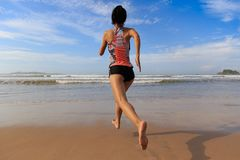 Fitness woman wear swimsuit running on beach. Young fitness woman wear swimsuit running on beach Royalty Free Stock Photos