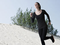 Woman in black running over sand dunes Stock Images