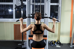 Young Fitness Woman Working Out Back On Machine In Fitness Center. Royalty Free Stock Photos