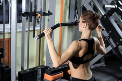 Young Fitness Woman Working Out Back On Machine In Fitness Center Stock Photos