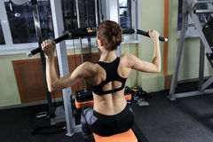 Young Fitness Woman Working Out Back On Machine In Fitness Center Royalty Free Stock Photography