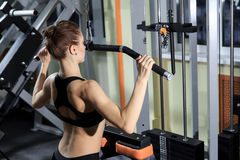 Young Fitness Woman Working Out Back On Machine In Fitness Center. Stock Images