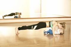 Mirroring young mother enjoying exercice in fitness studio with her baby boy Stock Images