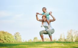 Young  woman working out with son on shoulders. Young fitness women working out outdoors while hoding son on shoulders Stock Photography