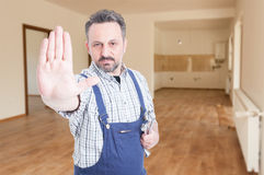 Young fitter with wrench in the room. Doing stop gesture with copy text space Royalty Free Stock Image