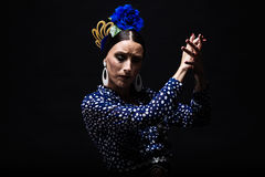 Young flamenco dancer in beautiful dress on black background. Royalty Free Stock Photography