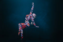 Young flexible blonde circus acrobat posing in studio in costume. Doing equilibre balance handstand on a cube. Stock Photography