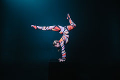 Young flexible blonde circus acrobat posing in studio in costume. Doing equilibre balance handstand on a cube. Royalty Free Stock Photo