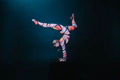 Young flexible blonde circus acrobat posing in studio in costume. Doing equilibre balance handstand on a cube. Stock Images