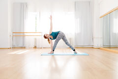 Young Flexible Blonde Woman In Utthita Trikonasana Triangle Pose Indoor Royalty Free Stock Images
