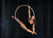 A young flexible girl performs the splits in the aerial ring. Aqua Studio shooting performances on a black background royalty free stock photo