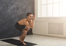 Young flexible man practicing yoga at gym. Young strong man practicing yoga, standing in flexible pose on mat in fitness class, making balance exercise, copy Royalty Free Stock Image