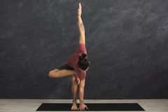 Young flexible man practicing yoga at gym. Young strong man practicing yoga, standing in flexible pose on mat in fitness class, making asana exercise, copy space Royalty Free Stock Photography