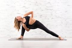 Fit woman doing utthita parsvakonasana yoga pose Stock Photos