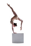 Young flexible woman posing on cube Royalty Free Stock Image