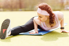 Young flexible woman stretching on fitness mat Stock Images