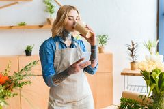 Young florist in apron drinking coffee from paper cup and using smartphone. In flower shop royalty free stock image