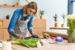 Young florist in apron writing word open on board. In flower shop stock photography