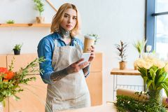 Young florist holding coffee to go and smartphone and looking at camera in flower. Shop stock photo