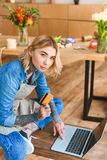 Young florist holding credit card and looking at camera while using laptop in flower. Shop stock photo