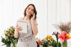 Young florist woman standing near table with different flowers i. N studio and calling to clients with notes in hand Royalty Free Stock Photo