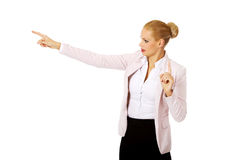 Young focus business woman explaining something and pointing at board or copyspace Royalty Free Stock Photos