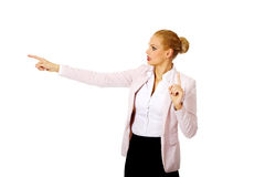 Young focus business woman explaining something and pointing at board or copyspace Royalty Free Stock Image