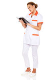 Young focus female doctor or nurse makes notes Stock Photo