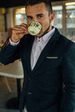 Young focused businessman drinking coffee in café. Indoor photo Stock Photography