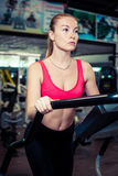Young focused female working out at gym jogging on a treadmill. Stock Photography