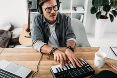 Man playing on MPC pad. Young focused man playing on MPC pad at workplace stock images