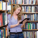 Young focused student using a tablet computer in a library Royalty Free Stock Photography