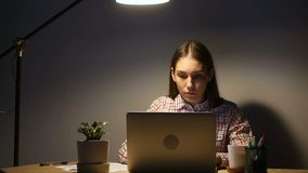 Young focused woman using laptop working late overtime on pc. Young focused woman using laptop working overtime on pc with documents late at home, student stock video